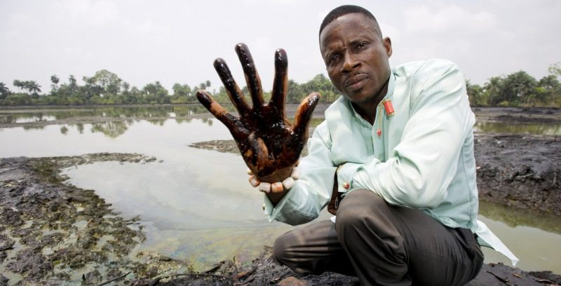 Eric Dooh, Goi community - plaintiff in court case against Shell - showing hand covered in oil pollution