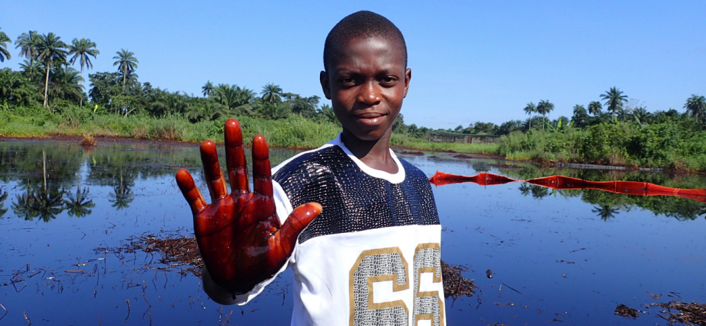 Boy holding palm covered in oil in Nigeria